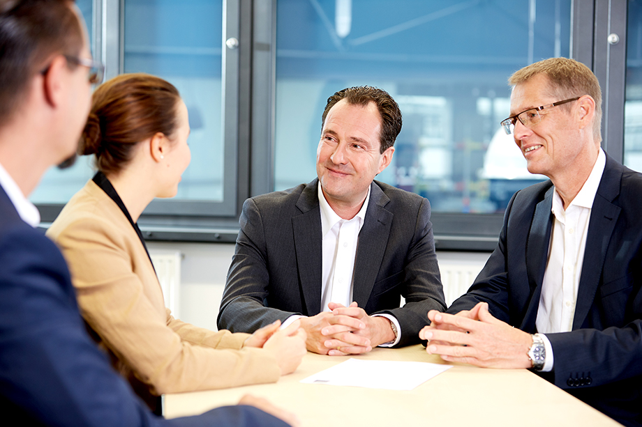 Photo: business meeting: three men and a woman in business attire talking around a wooden table in a modern office space
