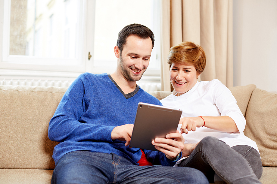 Photo: young couple on a couch looking at a tablet computer